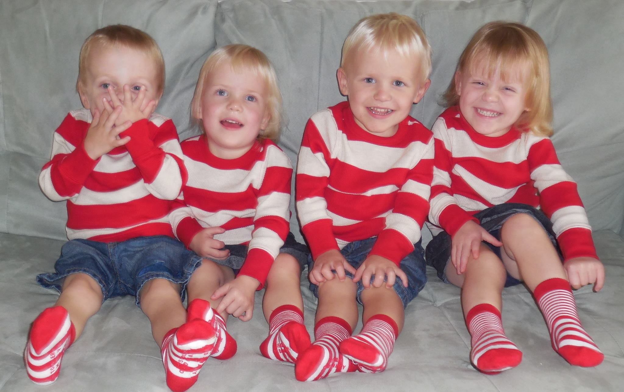 Larson quadruplet toddlers wearing matching red and white striped shirts
