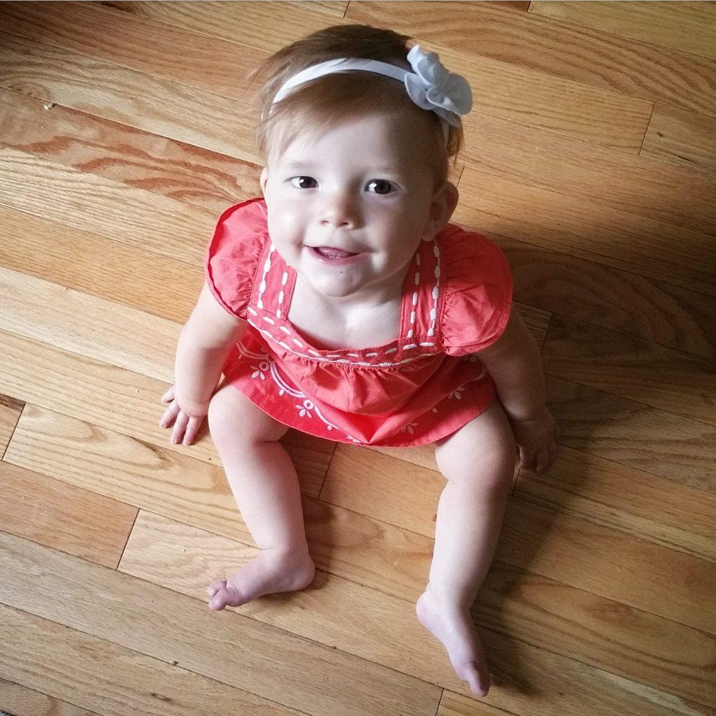 Price family little girl sitting on floor in red dress smiling