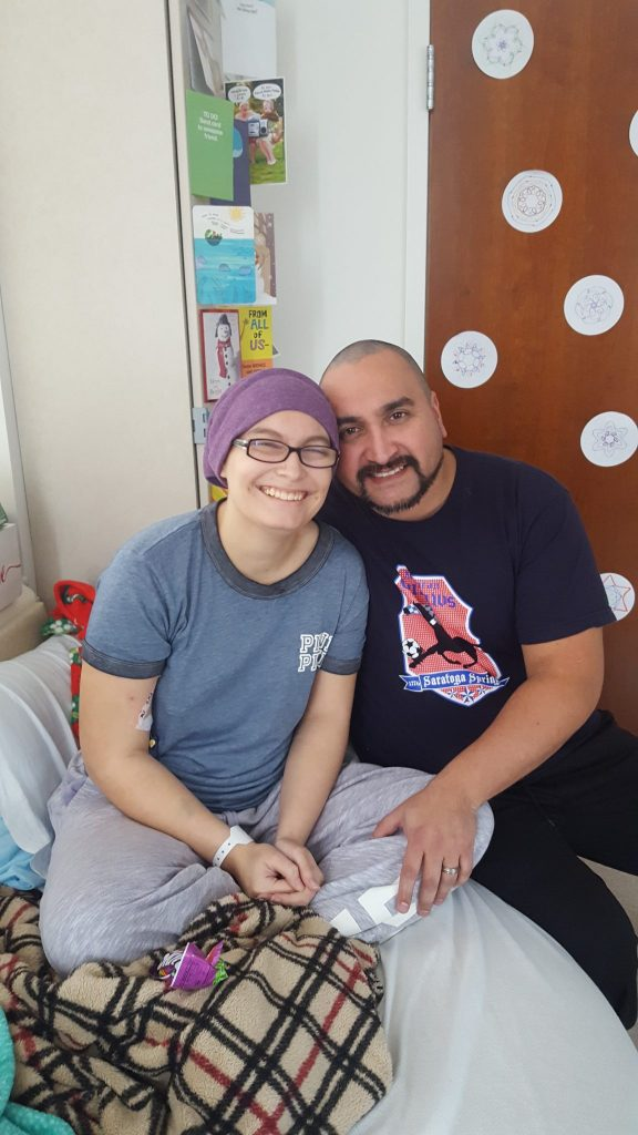 Father and daughter smiling and holding each other in a hospital room